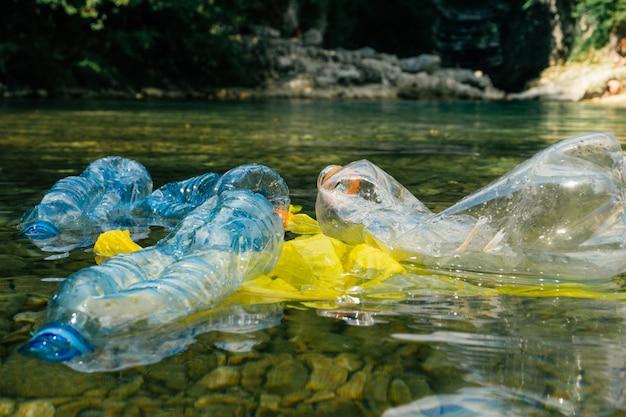 더러운 플라스틱 병 및 가방, 물에 플라스틱