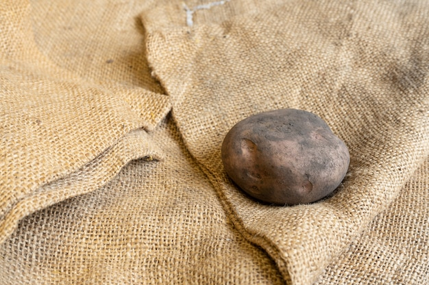 Dirty potato on the right side of a jute mat