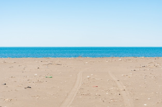 Грязный песчаный пляж черного моря. синее море, загрязнение окружающей среды