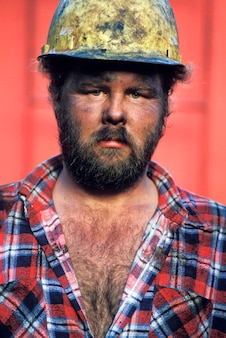 Dirty, serious, bearded construction worker in hard-hat