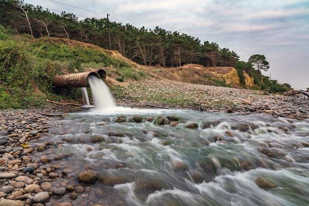Грязные сточные воды из заводской трубы, химическое загрязнение окружающей среды.