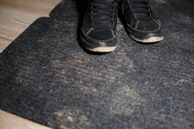 Грязная обувь стоит на черном ковре с разбросанным болотом