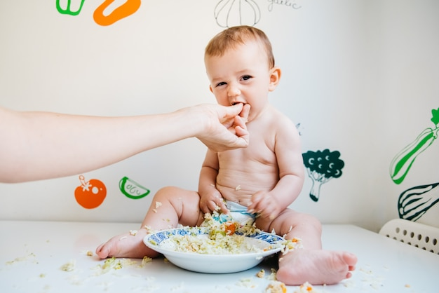Dirty and smiling baby on a white table being fed by his mother's hand, while laughing while trying the blw method.