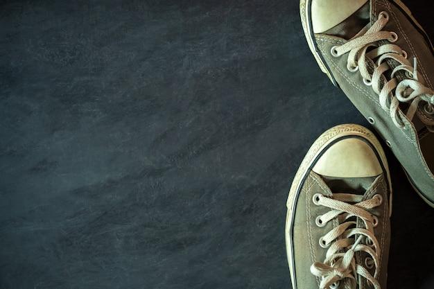 Dirty sneaker on black cement floor.