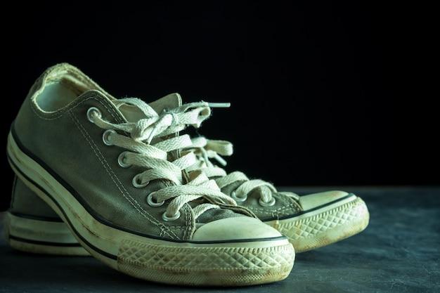 Dirty sneaker in darkness. closeup old sneaker on black cement floor.