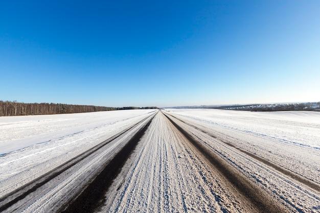 汚れた雪の茶色、冬の道路に横たわっている