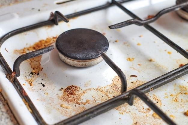 食べ物の残り物が付いている汚れたストーブ。脂っこい斑点、古い脂肪の汚れ、揚げ物の斑点、油の飛び散りがある汚れたガスキッチンのコンロ。