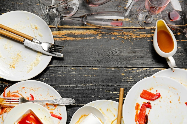 Dirty tableware on dark wooden table background