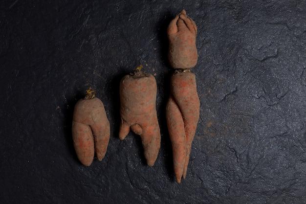 暗い織り目加工の石の背景に汚れた醜いニンジン奇妙で珍しい形の野菜