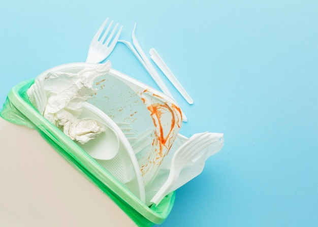 Posate e piatti bianchi sporchi nel cestino