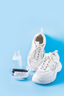 Dirty white sneakers with special tool for cleaning them on blue