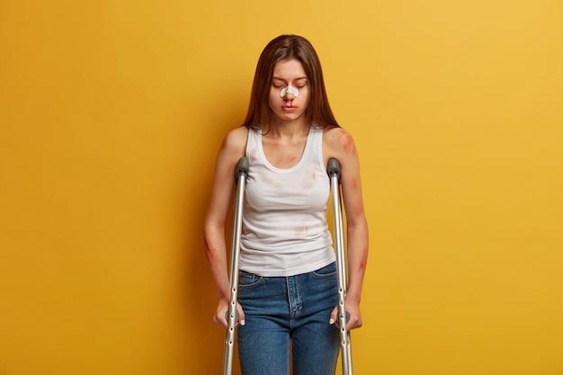 장애 및 건강 문제 개념. 불행한 여성은 사고로 심각한 외상을 입었고, 이동 보조 장치를 사용하고, 수술 후 첫 걸음을 내딛고, 내려다보고, 코에 석고를 끼고, 실내에서 포즈를 취합니다.