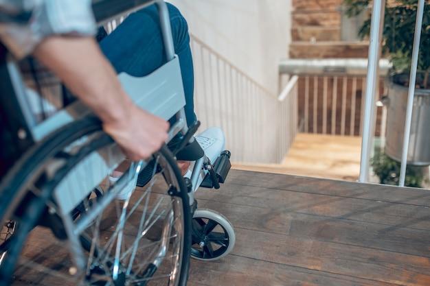 장애, 도전. 휠체어를 탄 남자는 계단 근처에서 멈추고 계단을 내려갈 수 없어 얼굴이 보이지 않습니다.