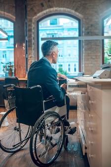 障害、雇用。日中のオフィススペースの机の引き出しに書類を置く車椅子のビジネスジャケットの男の背面図