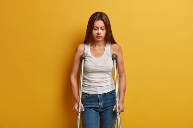 Disability and health problems concept. unhappy woman got serious trauma at accident, uses mobility assistance, takes her first steps after surgery, looks down, wears plaster on nose, poses indoor