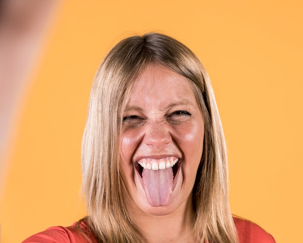 Disable woman sticking out her tongue against plain surface