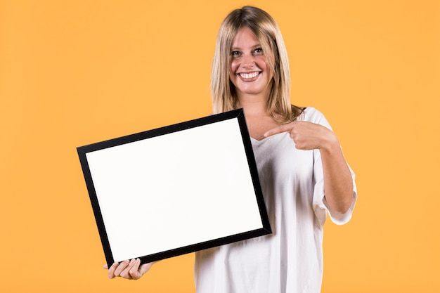 Disable young blonde woman pointing finger at empty white picture frame