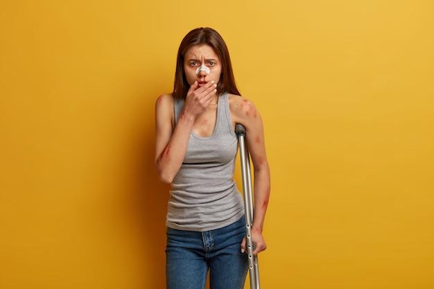 비활성화 젊은 여성 운전자는 출혈 얼굴, 코 심각한 부상에 붕대가 있습니다