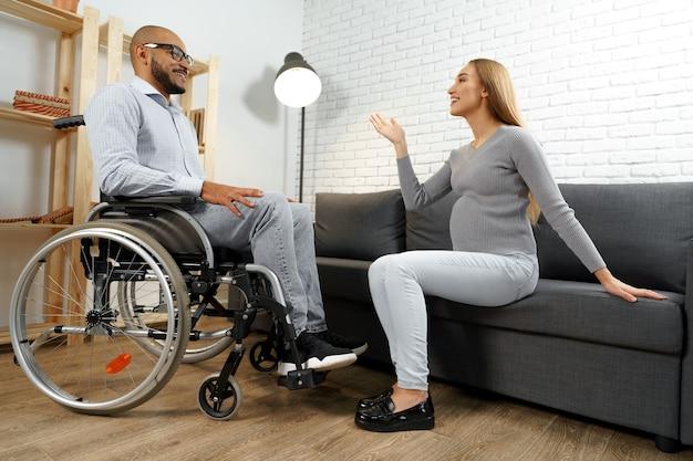 Афро-американский мужчина-инвалид в инвалидной коляске разговаривает со своей беременной женой в гостиной