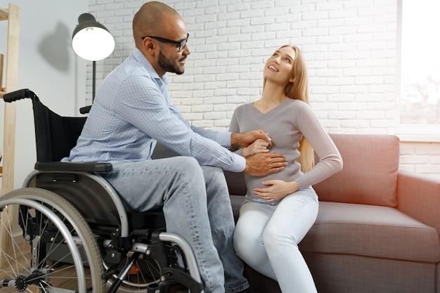 Афроамериканец-инвалид трогает живот своей беременной кавказской жены, отдыхая на ...