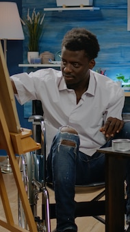 デザインを描くために鉛筆を使用して無効化されたアフリカ系アメリカ人の男