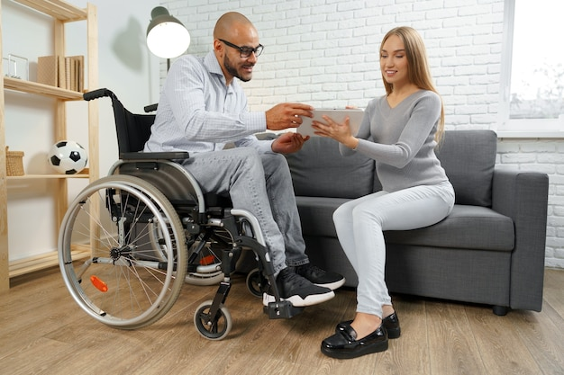 Disabled african american man in wheelchair and his pregnant caucasian wife watch something on digit...