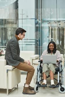 車椅子に座って、オフィスで彼女の近くに座っている彼女の同僚とラップトップで作業している障害のあるアフリカの女性