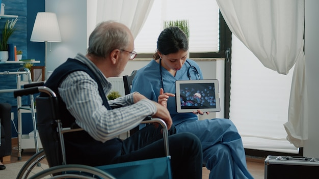 Disabled aged man looking at virus animation on tablet