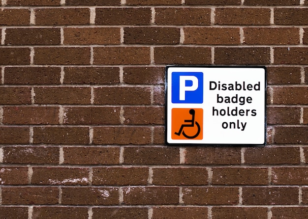 Disabled badge holders only sign on a brick wall