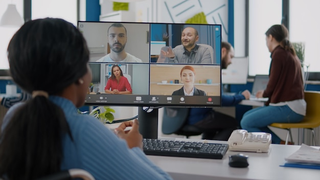 Disabled black manager discussing with remote team using videocall talking online during virtual mee...