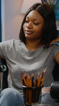 アートスタジオで花瓶のデザインを描く障害者の黒人女性