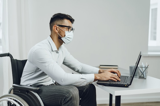 Disabled businessman doing his job and wearing medical face mask