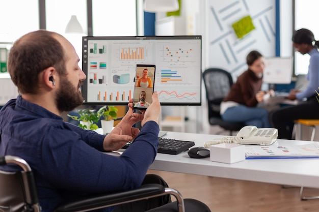Disabled businessman entrepreneur discussing with colleagues during video call