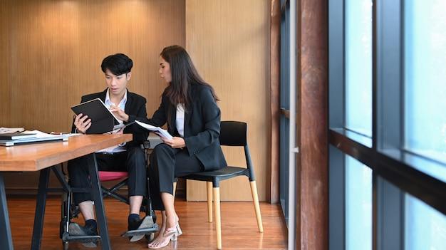 휠체어를 탄 장애인 사업가가 현대 사무실에서 동료들과 함께 일합니다.
