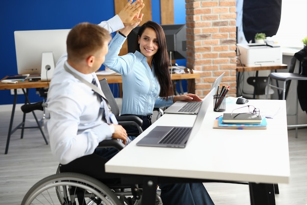 無効になっているビジネスマンがオフィスの作業テーブルで車椅子に座っているし、実業家に挨拶