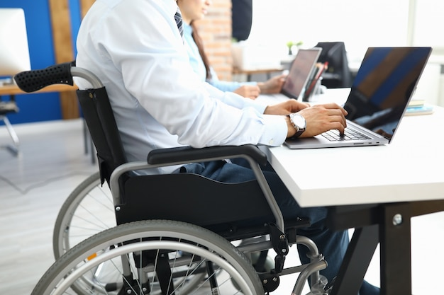 Disabled businessman sits in wheelchair in office and works at laptop