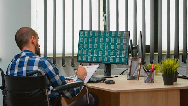 車椅子に座っている障害者のビジネスマンは、同僚と話し合っている営業所でメモを取りながら、金融経済データをチェックしています。現代の技術を使用した障害者フリーランサー。