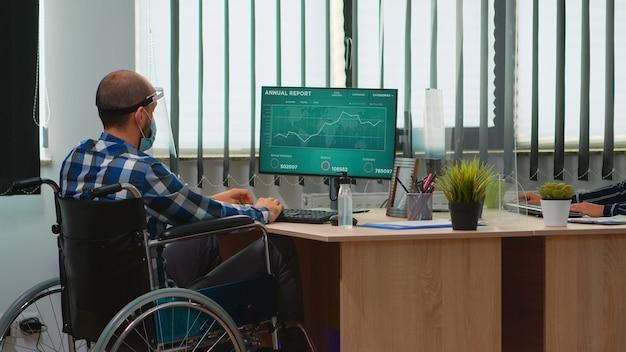 Uomo d'affari disabile seduto in sedia a rotelle con maschera di protezione che pulisce le mani prima di controllare i dati finanziari in un ufficio moderno. libero professionista disabile con visiera nel rispetto della distanza sociale