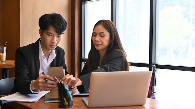 사무실에서 동료와 문서를 분석하는 장애인 사업가.