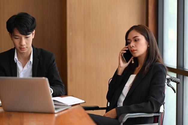 휠체어를 탄 장애인 여성 사업가가 현대 사무실에서 동료와 함께 앉아 있는 동안 휴대전화로 통화를 하고 있습니다.