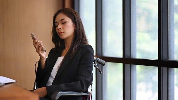 사무실에서 일하는 휠체어를 탄 장애인 사업가.