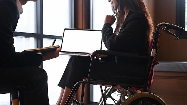 휠체어를 탄 장애인 사업가가 사무실에서 동료들과 함께 일하고 있습니다.