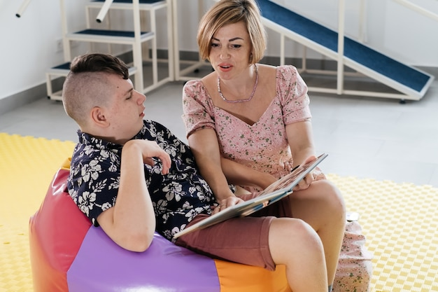 リハビリテーションを伝える本を読んでいる障害児