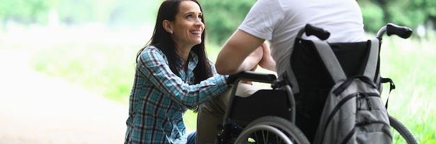 Disabled couple in love on a walk in park portrait. wife looks at her husband in love with eyes. rehabilitation disabled person after car accident concept