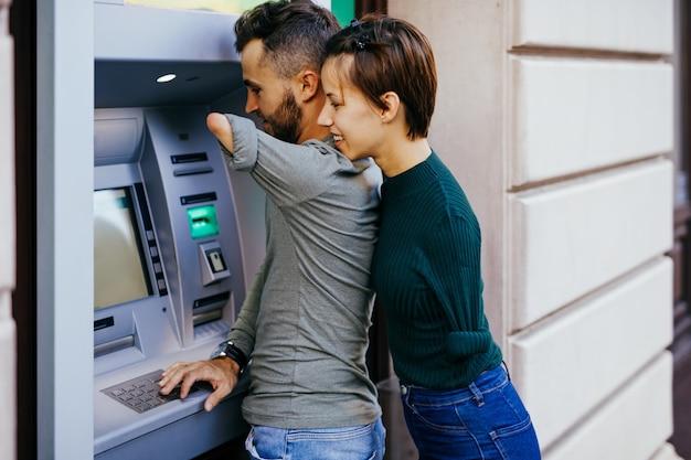 Пара инвалидов usinig банкомат на улице города.