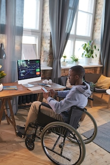 Disabled designer working online at home sitting at his workplace in front of computer monitor with software and talking online on the phone
