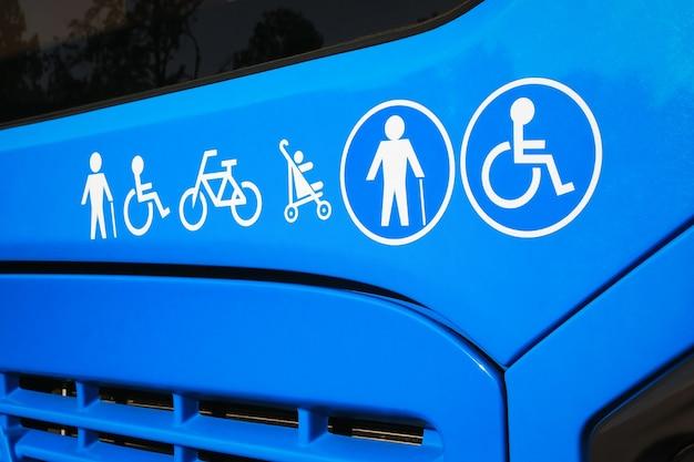 Инвалиды, пожилые люди, детская коляска, велосипедные знаки на городском автобусе