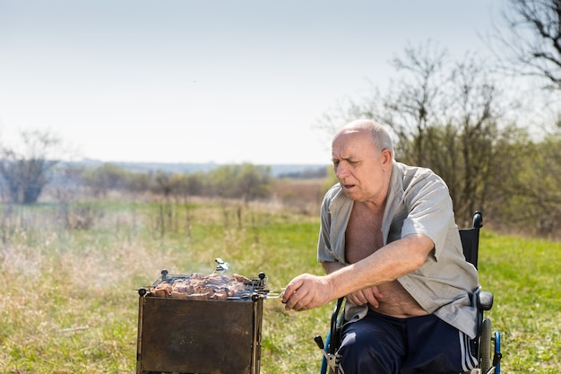 Disabled elderly man with unbuttoned shirt sitting on his wheelchair while grilling some meat sausages to eat at the park alone on a hot morning.
