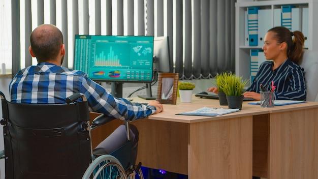 車椅子に座っている障害者の起業家が、同僚と話し合っている営業所のコンピューターで金融経済統計を分析している。現代の技術を使用して障害を持つビジネスマン