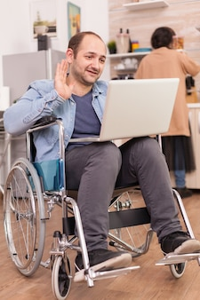 Disabled entrepreneur in wheelchair waving during a video call on laptop while wife is cooking lunch. disabled paralyzed handicapped man with walking disability integrating after an accident.